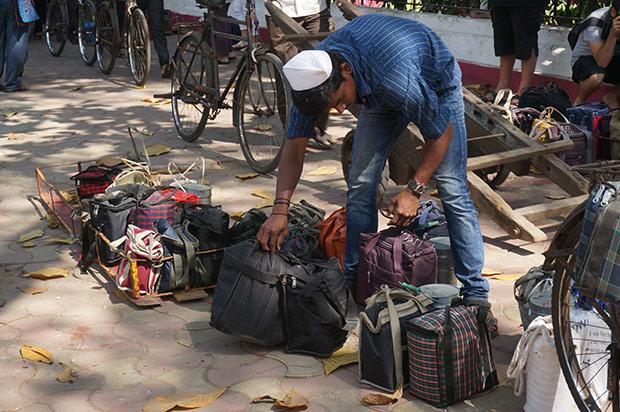 Un dabbawala trie son chargement devant la gare de Churchgate. Crédits : Clément Pairot