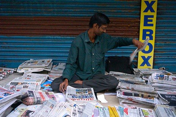 A la gare d'Andheri, des hommes s'occupent, comme tous les matins, dès l'aube, de trier les journaux. Crédits : Clément Pairot