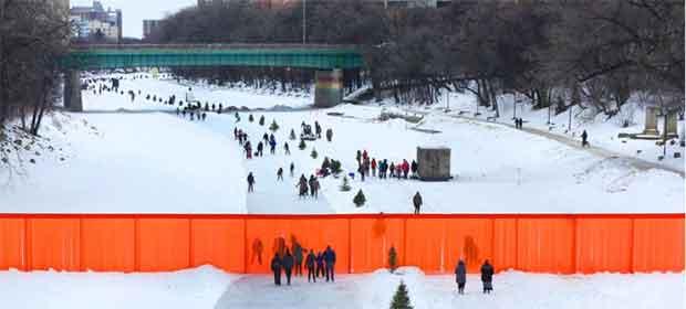 Le projet Open Borders prend la forme d'un mur de quatre mètres de long, en plastique rouge, qui borne une piste de patin à glace le long de la rivière Assiniboine, à Winnipeg, au Canada.