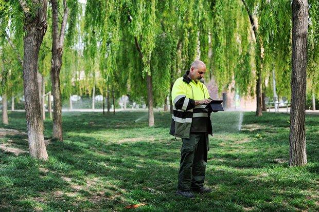 Un homme dans un parc qui grace a un ipad controle le systeme d arrosage