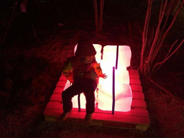 Un petit garçon assis sur des cubes lumineux à l'occasion de la fête des lumières à Lyon