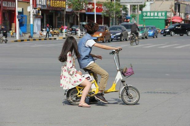 2 jeunes partagent le même vélo dans la ville