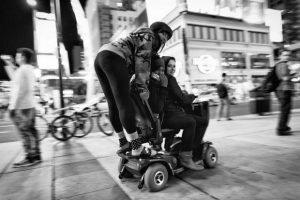 2 filles se déplacent avec un fauteuil roulant dans la ville