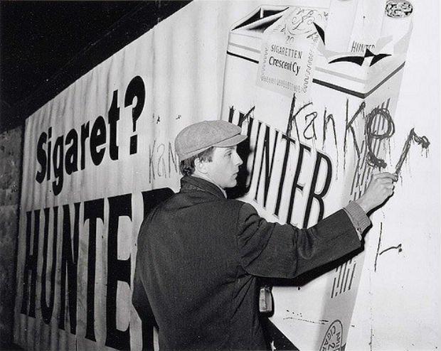 Robert Jasper Grootveld tague une publicité sur le tabac à Amsterdam, en décembre 1961