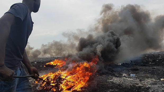 À Agbogbloshie, des hommes font des boules de câbles puis les brûlent pour récupérer le cuivre à l'intérieur