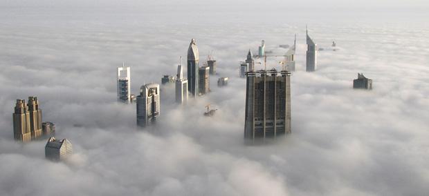 Vue sur les gratte-ciel de Dubaï au-dessus des nuages, depuis la tour Burj Khalifa (la plus haute du monde). Copyright : Captainofhope / Wikimedia
