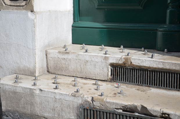 Boulons anti-SDF sur le perron d'un immeuble de Marseille (Bouches-du-Rhône).  Copyright : DocteurCosmos / Wikimedia