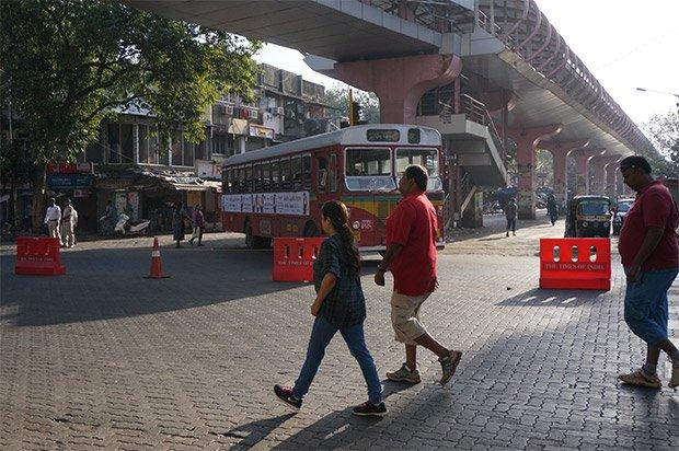 Arrivé au nord de la zone  piétonne, on passe sous une allée piétonne suspendue, rappelant la place qui est généralement allouée aux piétons pour garantir leur sécurité face à un trafic souvent tout puissant. « L'ambition de l'initiative « Reclaim your street », annoncée dans les journaux locaux, est de rendre la rue aux habitants et aux piétons. Le but est que les gens retrouvent un plaisir à déambuler dans la rue », ajoute Sree Kumar, responsable d'EMBARQ India. Crédits : Clément Pairot