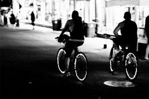 des cyclistes roulant dans une rue sombre