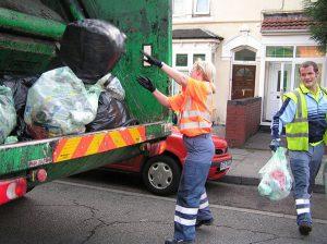 Une femme jetant des ordures dans un camion benne