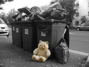 Un ourson devant des poubelles