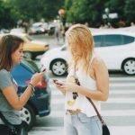 2 filles sur leur téléphone dans la rue