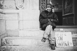 Un SDF assis sur une marche d'un bâtiment dans la ville
