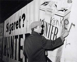 Robert Jasper Grootveld tague une publicité sur le tabac à Amsterdam, en décembre 1961 - Flickr/IISG
